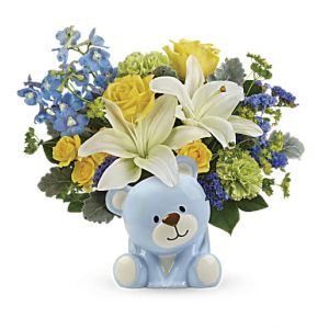"DiBella Flowers & Gifts Las Vegas - Yellow roses, yellow spray roses, white asiatic lilies, green carnations, light blue delphinium, and blue sinuata statice are arranged with bupleurum, dusty miller, and lemon leaf. Delivered in a blue Bundle of Love Bear. Approximately 13 1/2"" W x 12 1/2"" H"
