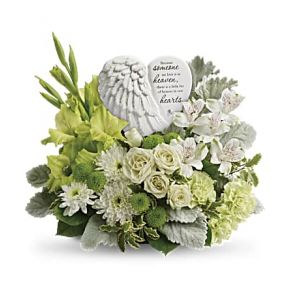 "DiBella Flowers & Gifts Las Vegas - Share your heart and show your love with this magnificent display of green and white blooms, gracefully surrounding an angel's wing keepsake with a loving message of sympathy. Message on sculpt reads: ""Because someone we love is in heaven, there is a little bit of heaven in our hearts."""