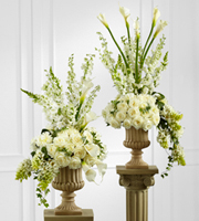 The FTD® Classic White™ Arrangement is a gorgeous arrangement set to add a touch of floral elegance to any space. White roses, open cut calla lilies, peonies, Star of Bethlehem, delphinium, larkspur, hydrangea, and snapdragon are arranged with interest and style to towering perfection. Seated in a classic resin urn upon a 3-foot pedestal, this arrangement will add to the joy and beauty of the day.