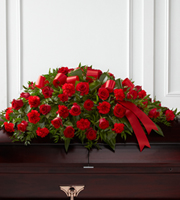 DiBella Flowers & Gifts Las Vegas - The Dearly Departed Casket Spray bursts with the love and passion that the deceased had for their life and loved ones. Rich red roses and carnations are gorgeously arranged amongst lush greens and accented with a red satin ribbon to create the ideal adornment for their casket at their final farewell service.
