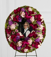 DiBella Flowers & Gifts Las Vegas - The FTD® Eternity™ Standing Easel is a stunning way to capture the memory of the departed at their final farewell service. Pink roses, purple carnations, lavender button poms, magenta gladiolus, variegated ivy and pittosporum greens are lovingly arranged to form a wreath surrounding a favorite picture of the deceased. Displayed on a wire easel, this arrangement is a moving way to honor their life and express your unending love and affection. ** Picture must be provided 8x10 2 days before delivery.