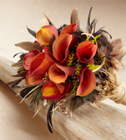 Free Spirit Bouquet is the perfect bouquet for a fall wedding, but is a stunning piece at any time of the year. Mango mini calla lilies are accented with red hypericum berries , solidago, and seeded eucalyptus and surrounded by feather picks and dried wheat stems. Wrapped in a raffia strands at the stems, this bouquet is a gorgeous departure from your everyday wedding bouquet.
