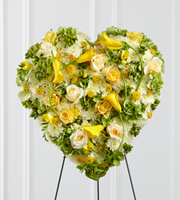 DiBella Flowers & Gifts Las Vegas - The FTD® Glowing Ray™ Standing Heart is an exquisite way to show your love and affection for the deceased. A collection of sunlit blooms, including, yellow roses, freesia, mini calla lilies, and button poms are accented with green hydrangea, white chrysanthemums, cream roses and green hypericum berries to form a sophisticated heart-shaped arrangement that offers a bright and elegant expression of caring kindness for their final goodbye. Displayed on a wire easel.