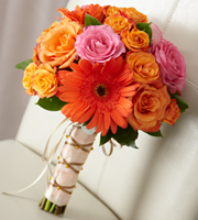 DiBella Flowers & Gifts Las Vegas - New Sunrise Bouquet is a dazzling display of floral elegance to help you celebrate your new life together.  Orange and fuchsia roses are brought together with orange spray roses and gerbera daisies to captivate with it's bright burst of color. Accented with lush greens and tied together at the stems with peach satin ribbon woven with gold and ivory satin ribbon, this bouquet has an unforgettable charm.
