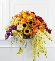 DiBella Flowers & Gifts Las Vegas - The FTD® Peaceful Tribute™ Arrangement is an elegant memorial that bursts with sun-kissed beauty. This three-sided arrangement brings together the varied elements, colors and textures of cream and red roses, purple stock, yellow mini calla lilies, orange Asiatic lilies, yellow gladiolus, sunflowers and lush greens to create a bright and brilliant display. Seated in a large round banana leaf basket, this arrangement will convey warm sentiments at their final farwell service.