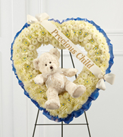 "DiBella Flowers & Gifts Las Vegas - The FTD® Precious Child™ Standing Heart is a beautiful way to commemorate a life lost too soon. White chrysanthemums and white button poms form a gorgeous white heart-shaped wreath lined around the outside with a bright blue ribbon. Accented with an ivory plush bear at the center and a white banner that reads, ""Precious Child,"" in gold metallic lettering, this sweet presentation is a lovely addition to their final farewell service. Displayed on a wire easel."