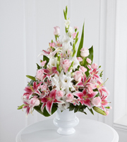 DiBella Flowers & Gifts Las Vegas - The Precious Peace Arrangement is an exquisite display of serene wishes and grace. Soft pink roses, Peruvian lilies and mini carnations are arranged amongst dazzling Stargazer lilies and white gladiolus, gorgeously accented with lush greens. Perfectly situated in a white plastic designer urn, this stunning arrangement will add to the beauty and elegance of their service or memorial.