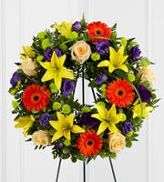 DiBella Flowers & Gifts Las Vegas - The FTD® Radiant Remembrance™ Wreath is a brilliant burst of color and light that honors a life full of joy and beauty. Crème de la Crème roses create a symbol of peace arranged amongst the vibrant hues of purple lisianthus, orange gerbera daisies, orange Asiatic lilies, green button poms, and a variety of lush greens, forming wonderful representation of a life well lived. Displayed on a wire easel.