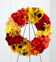 DiBella Flowers & Gifts Las Vegas - The FTD® Rural Beauty™ Wreath is a brilliant arrangement that expresses your grief in the jewel tones of dawn's first light. Peach, yellow, red, and orange bi-colored roses, burgundy carnations, yellow spider chrysanthemums, red gerbera daisies, sunflowers, orange Asiatic lilies, gold mokara orchids, and brown hypericum berries are brought together to form a wreath that honors a life well-lived. Displayed on a wire easel.