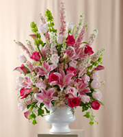 DiBella Flowers & Gifts Las Vegas - The FTD® Solemnity™ Arrangement is the perfect accent piece for the ceremony or reception. Hot pink roses pop against a backdrop of pink roses, larkspur, mini calla lilies, delphinium, hydrangea, and Oriental Lilies accented with Bells of Ireland and an assortment of fresh, lush greens. Perfectly arranged in a white plastic urn, this presentation will fill the space your exchange your vows or celebrate with the colors and sweetness of true love.
