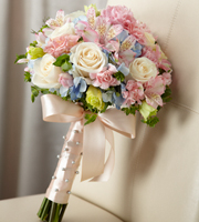 DiBella Flowers & Gifts Las Vegas - Sweet Innocence Bouquet blooms with sweet sentiments and endearing charm to get you to look your bridal best on your wedding day. Gorgeous cream roses, pink mini carnations, pink Peruvian Lilies, pink double lisianthus, blue hydrangea and bupleurum are brought together to create an unforgettable bouquet. Tied together with a soft peach satin ribbon accented with pixie pearl pins, this incredible styling culminates in a bow at the base of the bouquet.