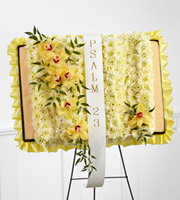 "DiBella Flowers & Gifts Las Vegas - The FTD® Taken Too Soon™ Bible Easel is a beautiful way to reaffirm the faith of the family and friends at their final tribute. Yellow cymbidium orchids and white chrysanthemums are delicately arranged atop an open styrene portfolio edged with a yellow satin ribbon and accented with a white ribbon which reads, ""Psalm 23,"" in gold metallic lettering, to create a wonderful display that offers comfort and beauty at their memorial service."