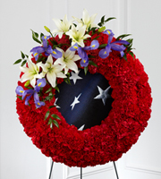 DiBella Flowers & Gifts Las Vegas - The FTD® To Honor One's Country™ Wreath is a vibrant patriotic tribute to a fallen soldier. Red carnations form a gorgeous wreath, accented with blue iris and white Asiatic lilies, which encircles a blue fabric with white stars on it, in character with the American flag, to create a stunning display for their final farewell service. Displayed on a wire easel. ** Flag must be provided.