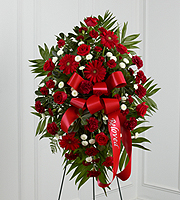 "DiBella Flowers & Gifts Las Vegas - The Treasured Memories Standing Spray is a rich and colorful way to express your unending love and devotion to the departed. An exceptional arrangement of red roses, burgundy carnations, burgundy mini carnations, red gerbera daisies and white button poms are accented with a variety of lush greens. A red ribbon with the word, ""Beloved,"" embossed in a gold metallic lettering, finishes this beautiful display for their final farewell service. Displayed on a wire easel."