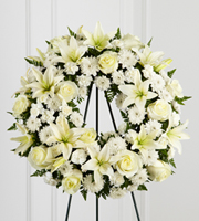 DiBella Flowers & Gifts Las Vegas - Treasured Tribute Wreath offers peaceful wishes of heartfelt sympathy with each delicate bloom. Bright white roses, Asiatic lilies, mini carnations and cushion poms are beautifully arranged to form an elegant accented with lush and vibrant greens. Displayed on a wire easel, this gorgeous tribute is a wonderful symbol of eternal life and sweet serenity. Approximately 22 inches in diameter.