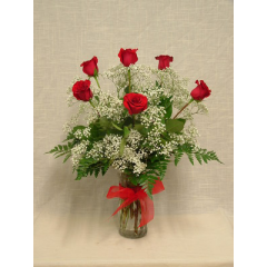 A half dozen premium long stem red roses arranged in a vase with filler and greenery.