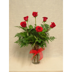 A half dozen premium long stem red roses arranged in a vase with greenery.