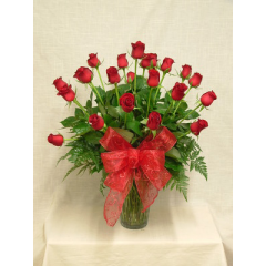 Two dozen premium long stem red roses arranged in a vase.