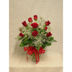 One dozen medium stem red roses arranged in a vase with filler and greenery.