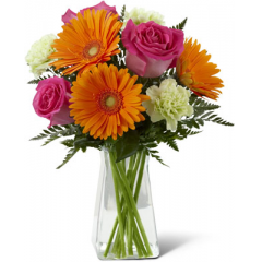 """The FTD Pure Bliss Bouquet is a blooming expression of happiness and joy set to brighten any day! Hot pink roses, orange gerbera daisies, light green carnations and lush greens are perfectly arranged in a clear gathered square glass vase to send a warm and cheerful sentiment to your special recipient. GOOD bouquet includes 9 stems. Approx.14""""H x 11""""W. BETTER bouquet includes 15 stems. Approx. 16""""H x 13""""W. BEST bouquet includes 21 stems. Approx. 19""""H x 14""""W. <br>"""