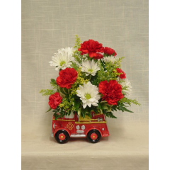 """Red carnations and mini carnations, golden aster, daisy poms, and greenery in a fire engine novelty ceramic. A great gift for any firefighter or any firefighter at heart!  Approx. 12""""H x 10""""W"""