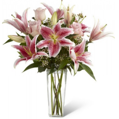 """Speak from your heart to theirs with a collection of pink vibrant blooms. Pale pink roses collaborate with the magic of Stargazer lilies displaying their fragrant fuchsia petals amidst waxflower accents. Beautifully arranged  in a clear square tapered glass vase, this bouquet sends your warmest sentiments with glamour and grace.<br><br>Approximately 20""""H x 14""""W"""