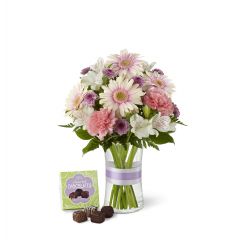 """The FTD Sweeter Than Ever Bouquet is full of blushing color and fresh beauty to create a remarkable gift. Pink gerbera daisies, pink carnations, lavender chrysanthemums, bi-colored pink and white Peruvian lilies and lush greens are perfectly situated in a clear glass vase accented with a lavender satin ribbon. Arriving with a 4-piece box of chocolate, this bouquet gives your special recipient a sweet wish that will surprise and delight them with its captivating grace. GOOD bouquet includes 10 stems. Approx. 13""""H x 10""""W. BETTER bouquet includes 13 stems. Approx. 14""""H x 11""""W. BEST bouquet includes 17 stems. Approx. 15""""H x 12""""W. <br>"""