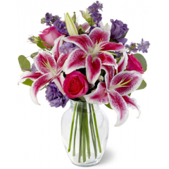 Bright hot pink roses, fragrant stargazer lilies, beautiful purple lisianthus and larkspur are arranged with silver dollar eucalyptus in an urn-shaped glass vase. This is a wonderful bouquet for anniversaries, birthdays, or any cause for celebration.<br>