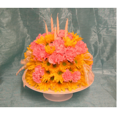 A birthday cake arrangement made from poms and carnations.  Give us a call to see what colors are available.