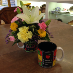 A great way to start off the year for any teacher!  Contains lilies, mini-carnations, carnations, button poms, and emile in a mug perfect for a teacher!  As shown in a mug that says 'Teaching is a work of HEART' other mug says '2 teach is 2 touch lives 4 ever'.