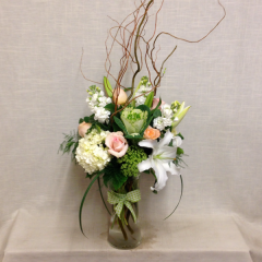 A 24in. tall arrangement of peach roses, hydrangea, lilies, kale, stock and accents.