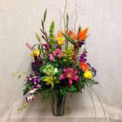 Standing 3 feet tall and 2 feet wide, this large arrangement of spectacular blooms contains some tropical flowers with a beautiful mix of bright flowers.  Arranged in an art-glass keepsake vase.