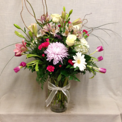 A beautiful collection of roses, tulips, cremons, hydrangea, lilies, gerberas, alstroemeria, and carnations in varying shades of pinks, hot pinks, and whites.  This arrangement is 30 inches tall, not including the curly willow.