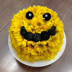 A smiling floral cake made from daisy poms and button poms.  This cake serves none, because it is not edible!  It will serve great for Birthdays, Congratulations, or any celebratory occasion!  Can also be made with lavender and white poms.