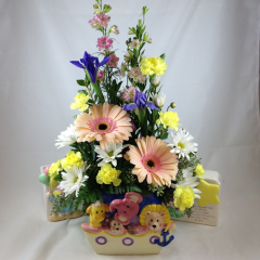 """A beautiful arrangement of iris, mini-carns, gerberas, larkspur, and poms in a music box novelty baby ceramic. Ceramics are gender neutral, and will vary, call the shop with specific requests.  This arrangement can be made specifically for a baby girl or baby boy in flower colors!  Just let us know!  Approx. 20""""H x 12""""W"""