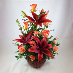 """An arrangement of lilies, roses, and mini-carnations in a basketball novelty ceramic.  Great for basketball fans!  We can make this arrangement in team colors if you give us a call!  Approx. 17""""H x 13""""W"""