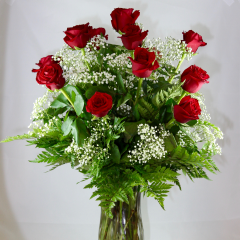 One dozen premium long stem red roses arranged in a vase with filler flower and greenery.