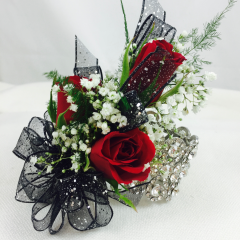 This glamorous wristlet has a beautiful rhinestone bracelet that can be worn after the dance is over.  Three red roses with your choice of ribbon and roses (please specify color in special instructions).  This pairs beautifully with our Rose Boutonniere with Rhinestone Holder.  Be the belle of the ball with this elegant addition.