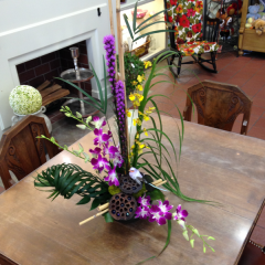 "A stunning display of dendrobium and oncidium orchids with liatris.  Includes a decorative bird, tropical greenery, lotus pods, and mossy accents. 26""H x 15""W"