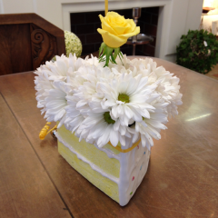 Daisy poms fill this birthday cake slice ceramic container.  One rose signifying a candle sits in the center.  Comes with an oversized mylar Happy Birthday balloon! (see picture!)