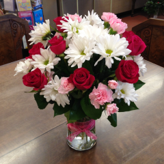 "Surprise your sweet with this romantic arrangement of hot pink baby roses, white daisy poms, and pink mini-carns.  15""H x 10""W"