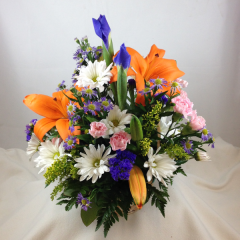 A natural-look basket arrangement of lilies, iris, daisy poms, monte casino, statice, and golden aster.