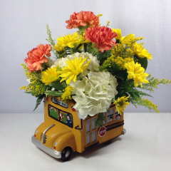 """A cute keepsake school bus ceramic with an arrangement of hydrangea, carnations, daisy poms, and solidago.  Approx 13""""H x 10""""W"""