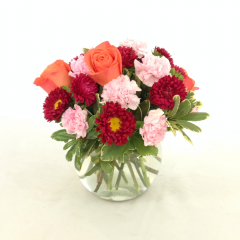 "Bouquet of orange roses, red matsumoto asters, pale pink mini carnations and greens. Arranged in a clear glass bubble bowl. Approx. 11""H x 12""W"