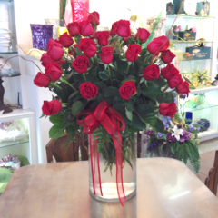A stunning display of 48 premium long stem red roses with a little bit of curly willow.