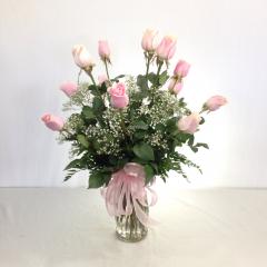 One dozen premium long stem light pink roses arranged in a vase with filler.