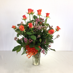 One dozen premium long stem orange roses arranged in a vase with filler.