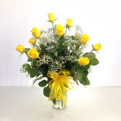 One dozen premium long stem yellow roses arranged in a vase with filler.