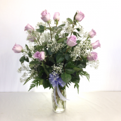 One dozen premium long stem lavender roses arranged in a vase with filler.