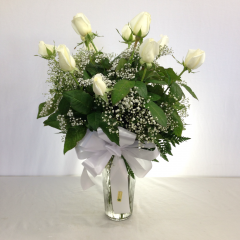 One dozen premium long stem white roses arranged in a vase with filler.